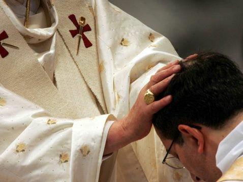 Sacerdote católico impone las manos en una ceremonia (¿Misa?) litúrgica